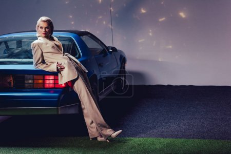 attractive and stylish woman in suit lying on retro car