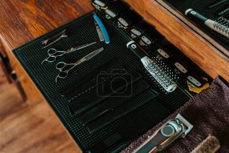 Photo pour Foyer sélectif de ciseaux tranchants près de la brosse à cheveux dans le salon de coiffure - image libre de droit