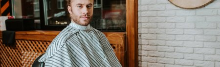 Photo for Panoramic shot of handsome bearded man sitting in barbershop - Royalty Free Image