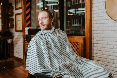 Photo pour Homme barbu en cape dénudée assis dans un salon de coiffure - image libre de droit