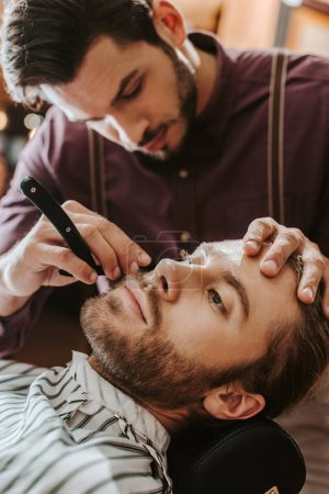 Photo for Selective focus of handsome barber shaving bearded man - Royalty Free Image