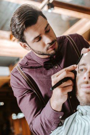 Photo pour Foyer sélectif de barbier rasage homme barbu dans le salon de coiffure - image libre de droit