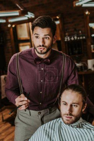 Photo for Stylish barber holding razor near bearded man in barbershop - Royalty Free Image