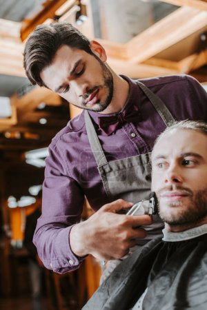 Photo for Handsome barber holding trimmer while shaving bearded man - Royalty Free Image