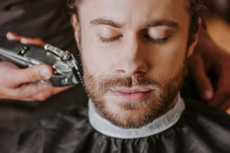 Photo for Selective focus of barber holding trimmer while shaving bearded man with closed eyes - Royalty Free Image
