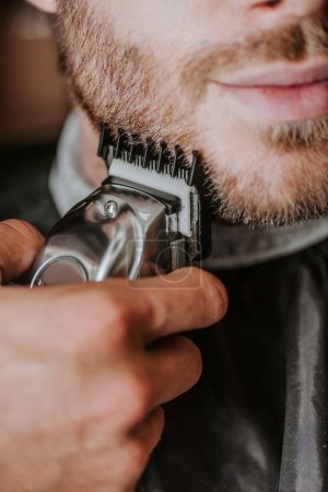 Photo for Cropped view of barber holding trimmer while shaving man - Royalty Free Image