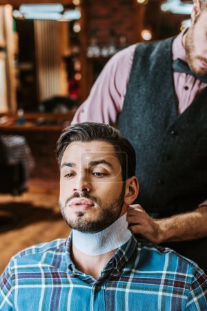 Photo for Barber fixing collar around neck of handsome bearded man - Royalty Free Image