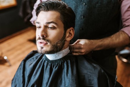 Photo for Barber fixing collar around neck of man in barbers cape - Royalty Free Image