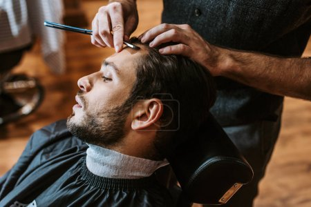 barber holding sharp razor while doing haircut to handsome man