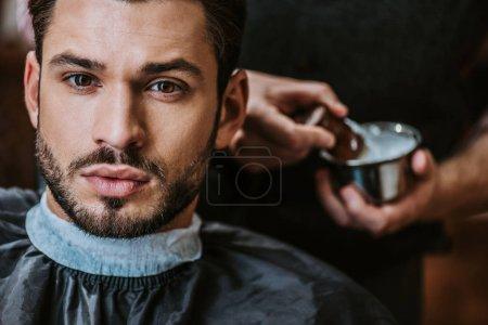 Photo pour Foyer sélectif de bel homme barbu regardant la caméra - image libre de droit