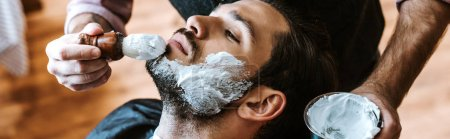 Photo pour Panoramic shot of barber applying shaving cream on face of bearded man - image libre de droit
