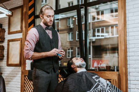 Photo for Handsome barber holding razor near bearded man with shaving cream on face - Royalty Free Image