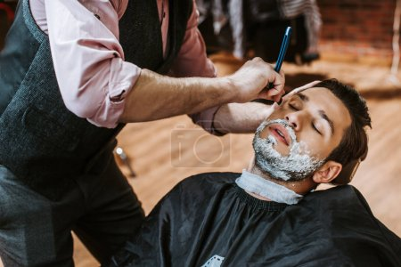 Foto de Barber shaving handsome man with shaving cream on face - Imagen libre de derechos