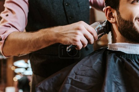 Photo for Cropped view of barber holding trimmer while styling hair of bearded man in barbershop - Royalty Free Image
