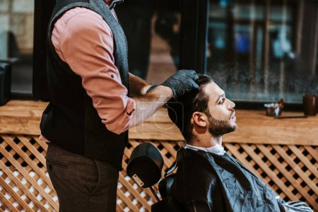 Photo pour Side view of bearded man sitting near barber in black latex gloves - image libre de droit