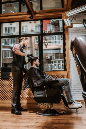 Photo pour Side view of handsome barber styling hair of man in modern barbershop - image libre de droit