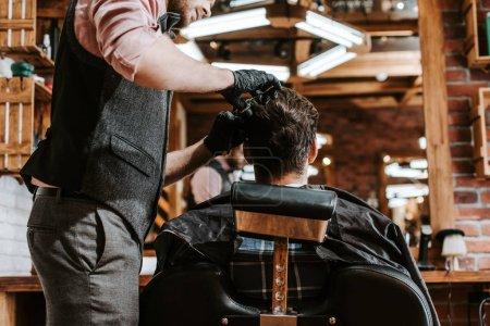 bearded barber cutting hair of man in barbershop
