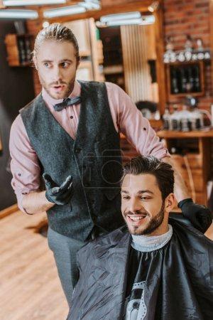 Photo pour Beau barbier geste près heureux homme dans salon de coiffure - image libre de droit