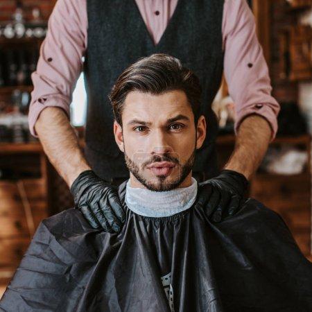 Photo pour Barbier en latex noir gants mettant les mains sur les épaules de l'homme dans un salon de coiffure - image libre de droit