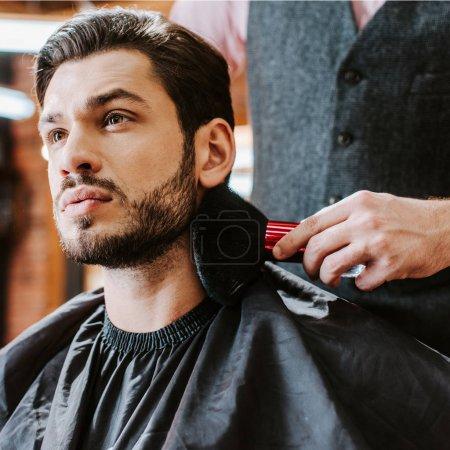 Photo pour Foyer sélectif du coiffeur tenant brosse cosmétique près du visage de bel homme barbu - image libre de droit