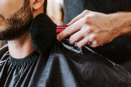 Photo for Cropped view of barber holding cosmetic brush near face of happy bearded man - Royalty Free Image