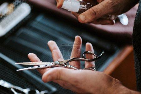 Photo pour Vue recadrée du coiffeur tenant pulvérisation antibactérienne près des ciseaux - image libre de droit