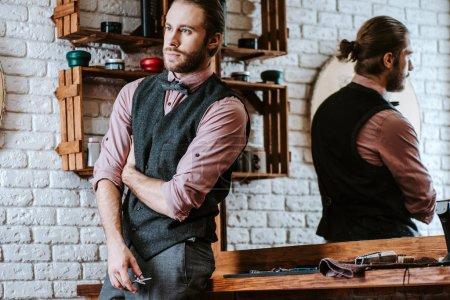Photo pour Barbu et beau barbier tenant des ciseaux dans le salon de coiffure - image libre de droit