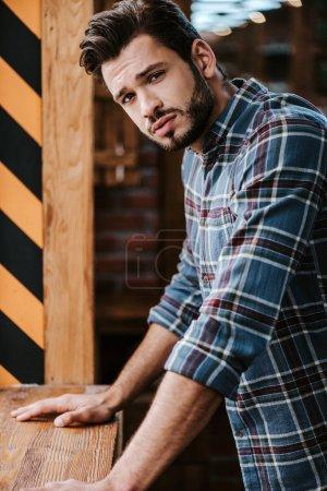 Photo pour Homme inquiet et barbu regardant la caméra dans le salon de coiffure - image libre de droit