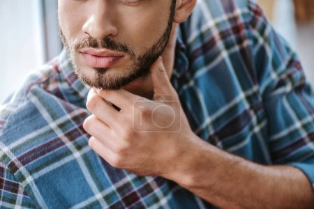 Photo pour Cropped view of bearded man touching face in barbershop - image libre de droit