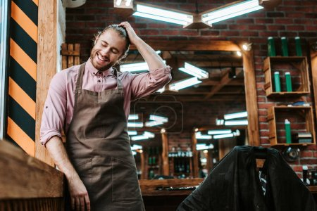 Photo for Selective focus of happy barber in apron touching hair in barbershop - Royalty Free Image