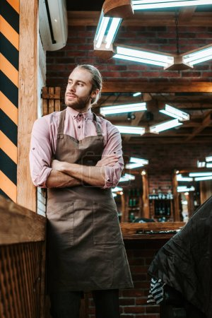 Photo for Selective focus of handsome barber in apron standing with crossed arms and looking away - Royalty Free Image
