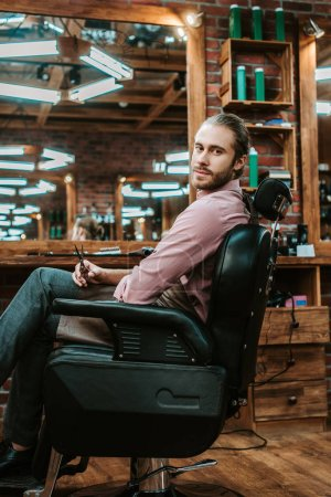 Photo pour Handsome and bearded barber looking at camera while sitting in armchair - image libre de droit
