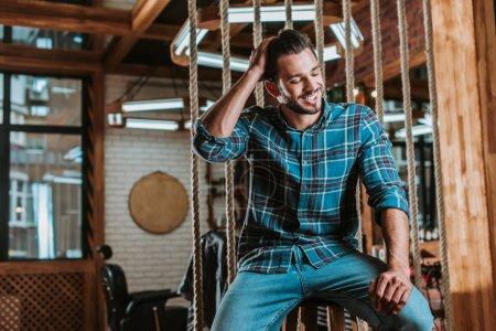 Photo pour Homme heureux assis et touchant les cheveux dans le salon de coiffure - image libre de droit