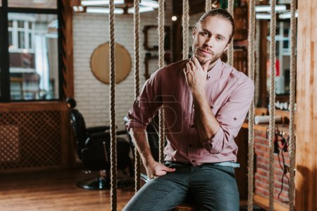 Photo pour Un homme barbu pensif regardant une caméra dans un salon de coiffure - image libre de droit