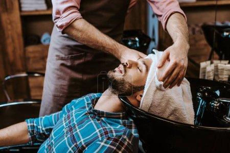 Photo pour Barbier tenant serviette blanche près de la tête de l'homme barbu avec les yeux fermés - image libre de droit