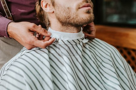 Photo pour Cropped view of barber fixing collar around neck of man - image libre de droit