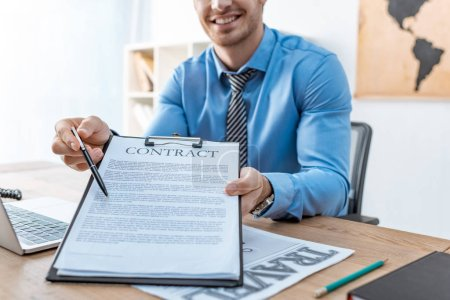 Photo for Cropped view of travel agent pointing with pen at contract on clipboard - Royalty Free Image