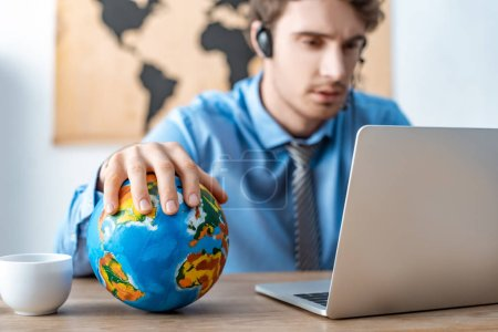 selective focus of travel agent touching globe while working near laptop