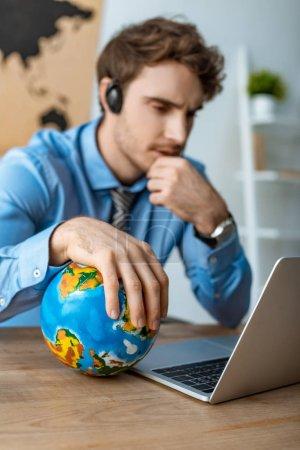 Photo pour Focalisation sélective d'un agent de voyages réfléchi qui touche le monde en restant assis au lieu de travail - image libre de droit