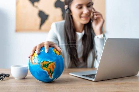 Photo pour Foyer sélectif de l'agent de voyage tenant la main sur le globe tout en travaillant sur le lieu de travail - image libre de droit
