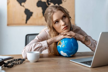 Photo pour Agent de voyages fatigué penchant sur le globe lorsqu'il est assis sur son lieu de travail - image libre de droit