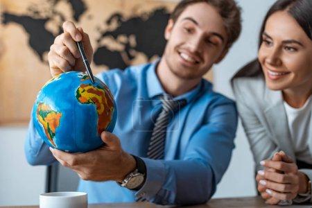 Photo pour Focalisation sélective d'un agent de voyages attirant se tenant près d'un collègue souriant pointant avec un stylo - image libre de droit