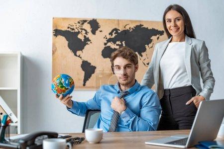 Photo pour Agent de voyage attrayant debout avec la main dans la poche près d'un collègue tenant le globe - image libre de droit