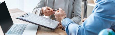 Photo pour View croisée de l'agent de voyage donnant le contrat et le stylo au client, photo panoramique - image libre de droit