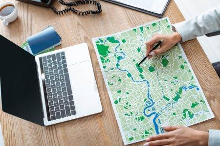 Photo pour Vue recadrée de l'agence de voyage pointant avec stylo sur la carte sur un bureau en bois - image libre de droit