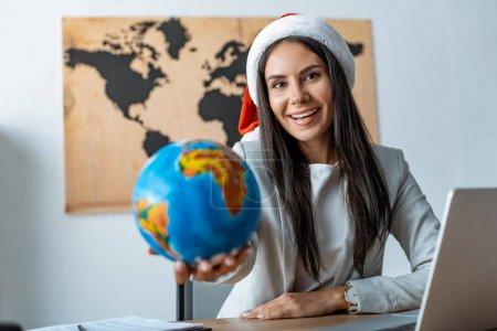 enfoque selectivo de agente de viajes sosteniendo globo y sonriendo a la cámara
