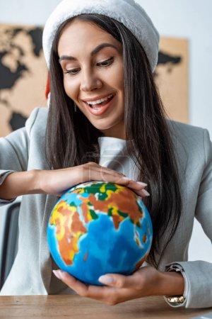 Photo pour Happy travel agent tenant le globe pendant qu'il est assis au travail - image libre de droit