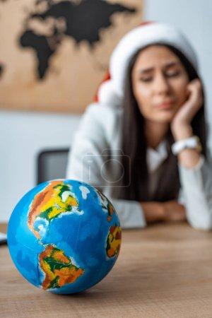 Photo pour Focalisation sélective de l'agent de voyages pénible près du globe sur le lieu de travail - image libre de droit