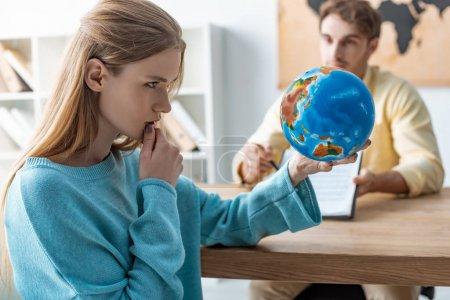 Photo pour Focalisation sélective d'une jeune femme réfléchie regardant la planète tout en s'assoyant près d'un agent de voyages - image libre de droit