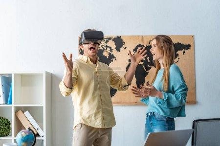 Photo pour Un agent de voyages souriant regardant un client excité à l'aide d'un casque vr - image libre de droit